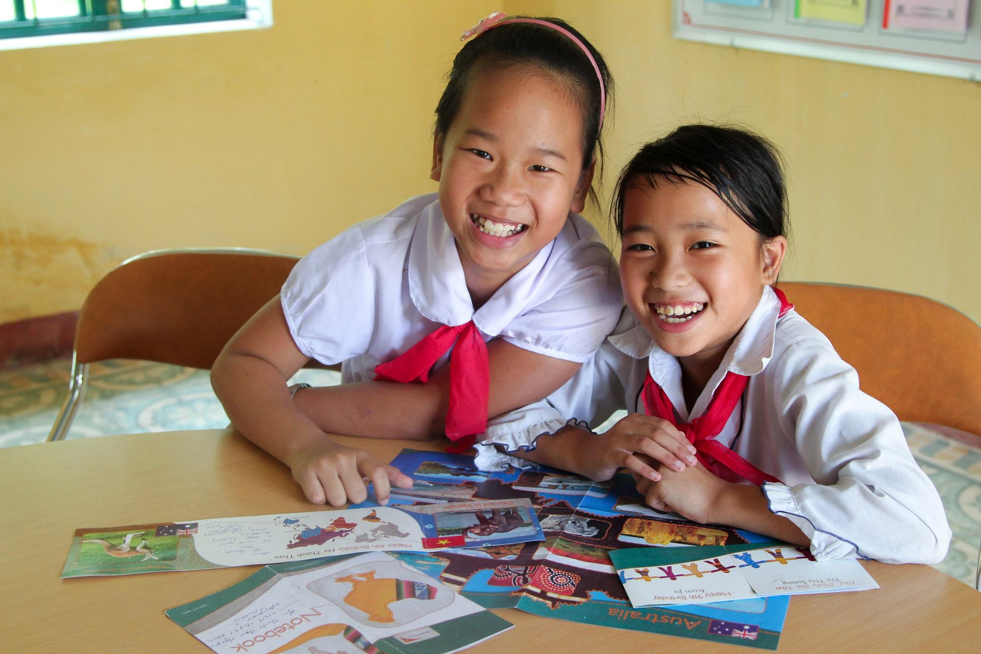 two sponsored girls smile, displaying cards they got from their sponsors